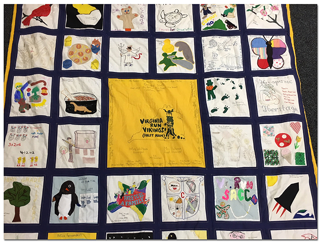 Photograph of a portion of the quilt. 27 squares are fully visible and include images of a cardinal, a bear puppet, a butterfly, a rocket, a penguin, a tree, a dinosaur, a leprechaun, dogwood blossoms, a turtle, a whale, and a manatee. The center panel, in yellow with blue lettering, is the image that appears on one of Virginia Run's first yearbooks, that of a cartoon Viking running across a map of the state of Virginia with the words: Virginia Run Vikings, First Run!