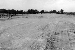 Black and white photograph of the construction of Virginia Run Elementary taken on May 27, 1988. The school lot has been graded. There are some trees in the far distance, but much of the image shows bare flattened earth.