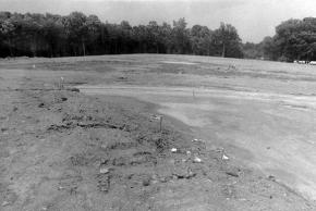 Black and white photograph of the construction of Virginia Run Elementary taken on July 20, 1988. Similar to the previous photograph except wooden stakes have been placed in the ground marking the outlines of the foundation prior to the pouring of the concrete slab.