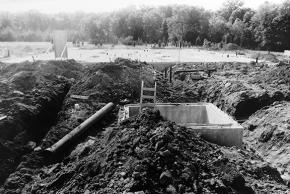 Black and white photograph of the construction of Virginia Run Elementary taken on August 24, 1988. Foundation work has begun. Several large holes and trenches have been dug in the earth. Some metal piping is visible.
