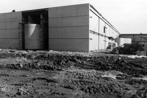 Black and white photograph of the construction of Virginia Run Elementary taken on December 29, 1988. The building has come quite a long way in four months. The exterior walls are almost all in place. There is some scaffolding visible in one section and heavy construction equipment is seen on the far right. The school grounds are muddy and water has pooled in puddles.
