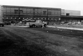 Black and white photograph of the construction of Virginia Run Elementary taken on March 29, 1989. An asphalt driveway has been paved. There is scaffolding running along the length of one side of the building. A construction worker can be seen walking away from his truck parked in the center of the photo.