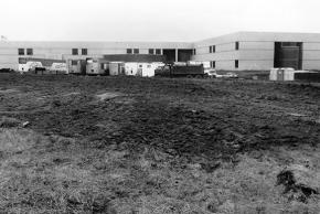 Black and white photograph of the construction of Virginia Run Elementary taken on April 29, 1989. Again, from the vantage point of what will be the main driveway, but it has not been paved yet. Construction vehicles and trailers fill the space in front of the main entrance. The exterior walls look almost complete.