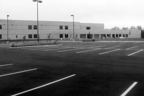 Black and white photograph of the construction of Virginia Run Elementary taken on August 29, 1989. Ready for opening day. The building is complete, the parking lot paved and painted, and all the landscaping is in place. The parking lot is empty.