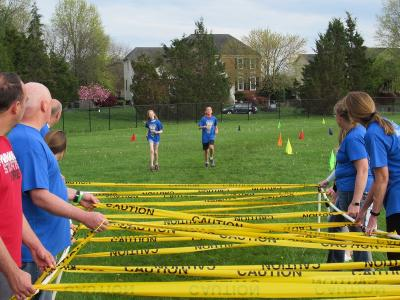 Some runners approach one of the obstacle stations